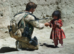 A Special Forces soldier gives a young Afghan girl some food after he took part in a search of her village Friday in Zabul Province. The SF and AFghan National Army soldiers were looking for Taliban fighters there, but their search turned up none.